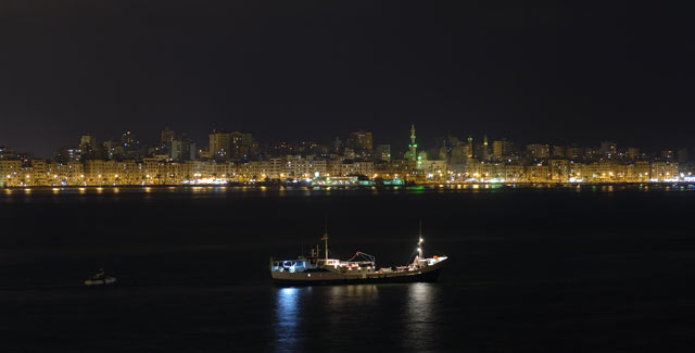 The expedition ship Princess Duda in front of Alexandria's night skyline.