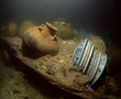 Between two bulkheads of the junk, still uncovered can be seen a pile of porcelain dishes and several jars. The partition between two bulb-keels can be observed in the foreground.