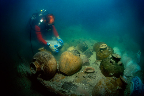 A diver frees jars from sediments with the help of a water dredge on the wreck of the Santa Cruz junk.