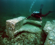 An archaeologist measuring the feet and other fragments of a colossal statue after preliminary cleaning on site at Thonis-Heracleion in the Bay of Aboukir.