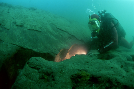 Diver examining a fault-like feature in the mud-base of a trench near an imposing monument at East Canopus, probably the temple of Serapis.